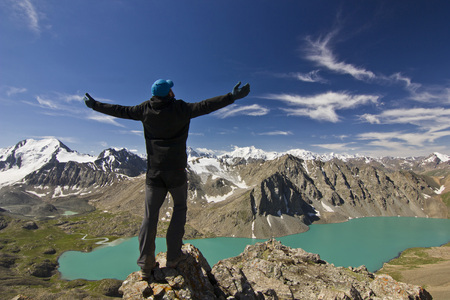 man in black jacket standing with hands up above blue calm mountain lake Alakol with mountains surrounded Stock Photo