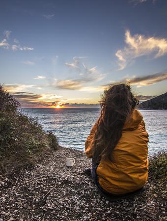 girl in yellow jacket sitting near seashore at sunset Stock Photo