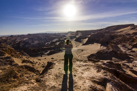 girl standing on a cliff in salty Moon valley in atacama desert at sunset Stock Photo