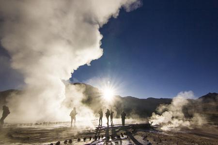Stoom van geyser tatio tegen zon bij zonsopgang met mensen staande