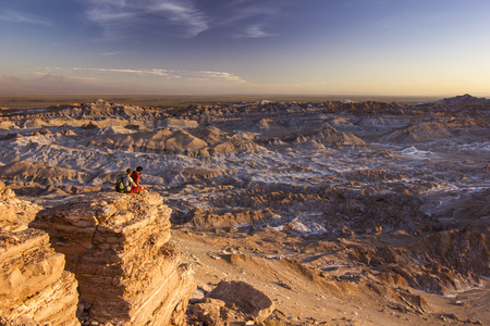 man sitting on a cliff in salty Moon valley in atacama desert at sunset Stock Photo