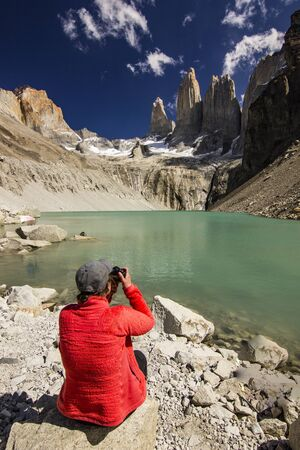 girl in red jacket sitting on the stone above lake in patagonia