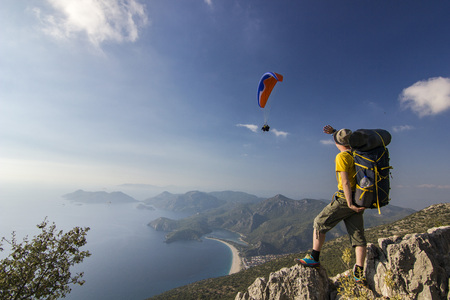 tourist standing on a cliff in mountains with paraglider in air