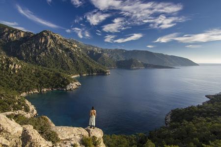 man standing on a cliff in mountains near mediterranean sea