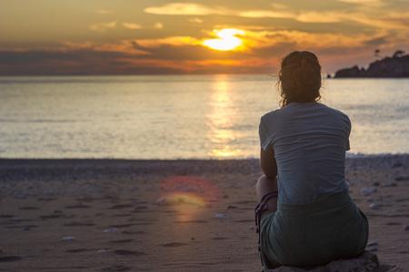 girl sitting on sandy beach near mediterranean sea at sunset