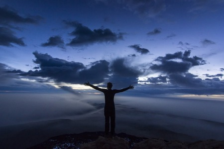 man with hands up on top of teide volcano at sunrise