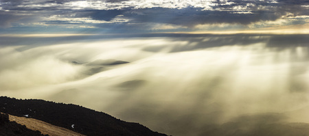 sunrise from teide volcano with transparent fog above mountains