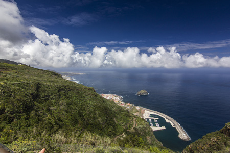 view on blue ocean with white clouds from green hill 写真素材