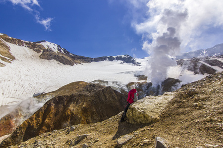 girl sitting near steaming crater of active volcano covered by snow