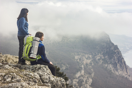 couple sitting on a cliff in mountains looking forward