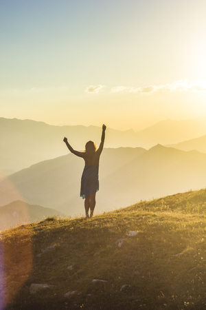 girl in dress with hands up standing on grass in sunset mountains