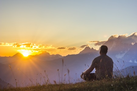man sitting on grass at sunset in mountains