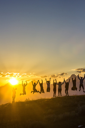 group of people with hands up jumping on grass in sunset mountains