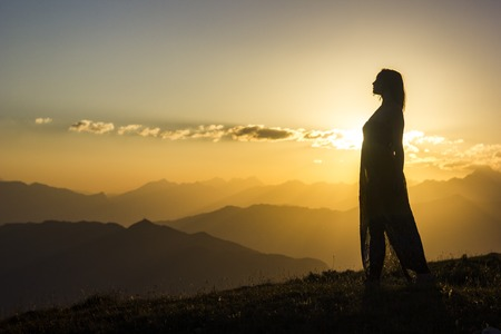 silhouete of girl in dress standing on grass in sunset mountains