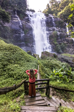 girl standing in forest near huge waterfall in jungle of thailand