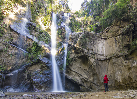 man standing in forest near huge waterfall in jungle of thailand 写真素材