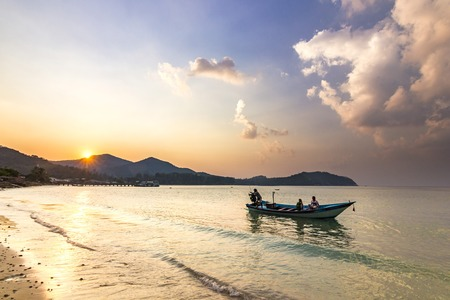 ocean seashore with palms and boat on water at sunset in Phangan island 写真素材