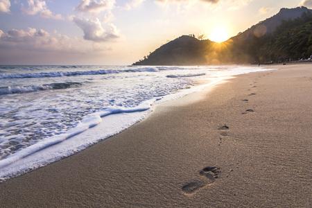 footprints on sand of running girl on sandy seashore at sunrise in thailand