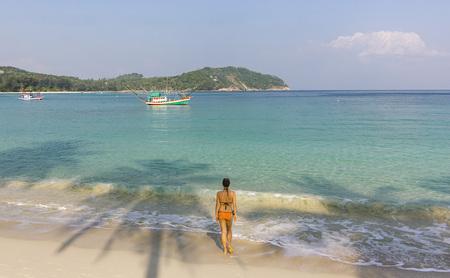 girl standing on sandy ocean seashore at sunrise in phangan island