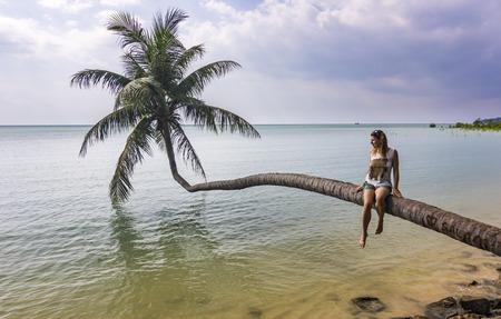 girl sitting on curved palm near ocean in Phangan island