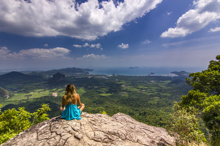 girl sitting on rock at daylight with mountains below 写真素材