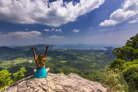 girl with hands up sitting on rock at daylight with mountains below