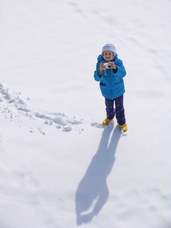 snowscene: Young girl with photocamera on the snow field