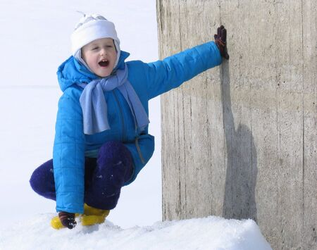snowscene: Young girl near the concrete wall