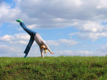 Somersault on grass on the sky&clouds background