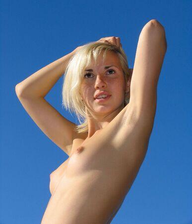 femme se deshabille: Jeune fille blonde sur le fond de ciel bleu -