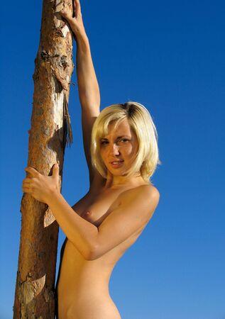 Girl near the Pine tree trank on the blue-sky background Stock Photo - 278411