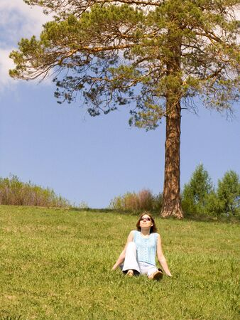 Girl on the lawn under the pine tree photo