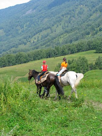altay: Young girls traveling in Altay mountains on horses