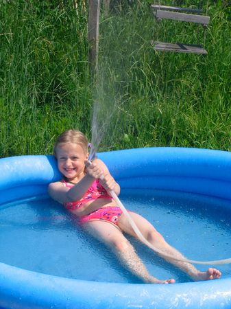 Smiling girl in the swimming-pool playing with the watter photo