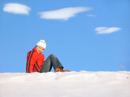 snowscene: Young girl sitting on snow  under blue sky and clouds
