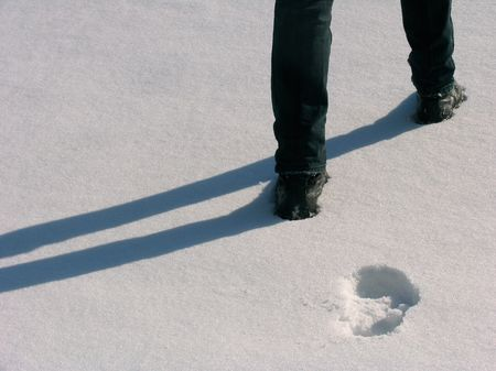 Man legs with the footprints on the snow Stock Photo