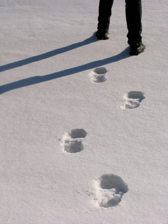 Man legs with the footprints on the snow photo