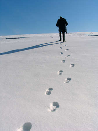 Footprints on the snow and hiking man photo
