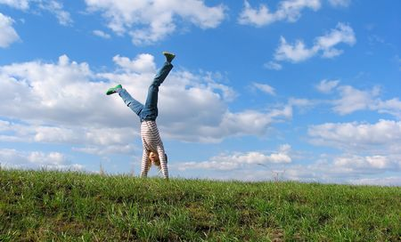 Somersault on grass on the sky & clouds background