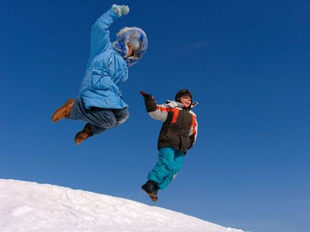 Boy and Girl jumping over snow on blue sky photo