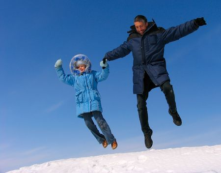 Happy family jumping over snow under blue sky