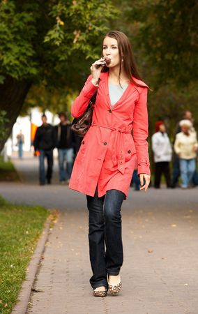Girl walking along footpath and eating chocolate icecream photo