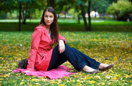 Portrait of beautiful girl siting on the autumn leaves  photo