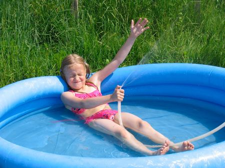 Smiling girl in the swimming-pool playing with the watter Stock Photo