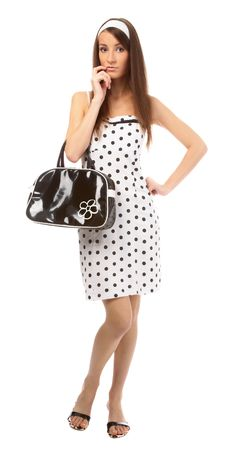 beautiful model in polka-dot dress with black bag tries to recall something photo