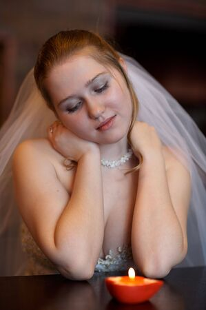 marriageable: Young bride sitting before burning candle