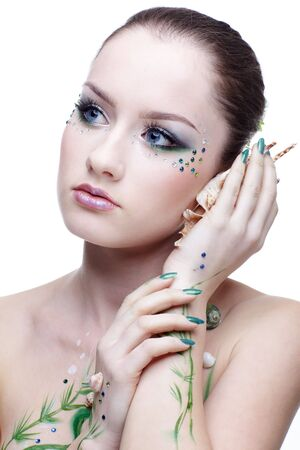 portrait of beautiful girl with mermaid bodyart listening to the sounds in shell photo