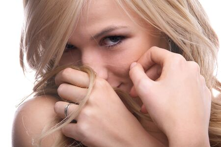 close-up portrait of beautiful blonde model looking shy and hiding her smile in a strand of hair photo