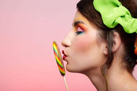 portrait of beautiful girl kissing big lollipop photo
