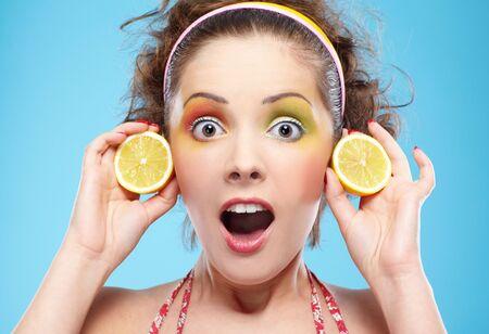 portrait of beautiful shocked girl posing with lemon photo